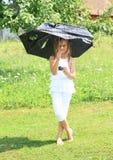 Mädchen im Weiß mit defektem blauem Regenschirm Lizenzfreie Stockbilder