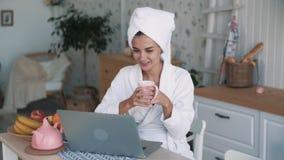 Mädchen im weißen Bademantel, mit Tuch auf dem Kopf, der Videoschwätzchen auf Laptop, Zeitlupe hat stock footage
