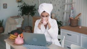 M?dchen im wei?en Bademantel, mit Tuch auf Hauptarbeiten ?ber Laptop, Zeitlupe stock video