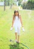 Mädchen im weißen Gehen durch Berieselungsanlage Lizenzfreie Stockfotos