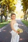 Mädchen im weißen Kleid in der Gasse im Park Lizenzfreie Stockbilder