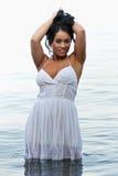 Mädchen im weißen Kleid durch den Strand Stockfotografie