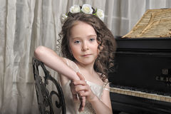 Mädchen im weißen Kleid am Klavier Lizenzfreies Stockbild