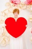 Mädchen im weißen Kleid mit rotem Herzen in den Händen Lizenzfreies Stockbild