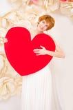 Mädchen im weißen Kleid mit rotem Herzen in den Händen Stockbilder
