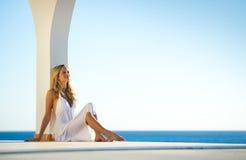 Mädchen im weißen Kleid am Sonnenuntergang durch das Meer 4 Stockbild