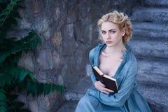 Mädchen im Weinlesekleid, das mit einem Buch auf der Treppe sitzt Stockbild
