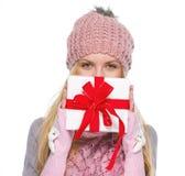Mädchen im Winter kleidet das Verstecken hinter dem Weihnachten, das Kasten darstellt Lizenzfreie Stockfotografie