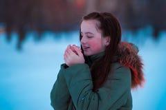 Mädchen im Winterfoto Weiße Schneeflocken auf einem blauen Hintergrund stockfotografie