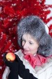 Mädchen im Winterpelzmantel, der mit Apfel aufwirft Lizenzfreie Stockfotografie