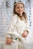Mädchen im Winterurlaubkleid mit Spielzeugkaninchen Stockfotos