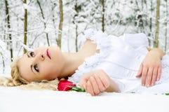 Mädchen im Winterwald mit einer Rose Lizenzfreies Stockfoto