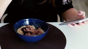 Mädchen isst Brei zum Frühstück und benutzt das Telefon stock video footage
