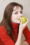Mädchen isst einen Apfel lizenzfreie stockfotografie