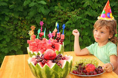 Mädchen isst Frucht im Garten, glückliche Geburtstagsfeier Stockfoto