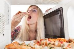 Mädchen isst Pizza aus der Mikrowelle heraus Lizenzfreie Stockfotos