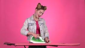 Mädchen ist reiche und bügelnde Rechnungen Rosa Hintergrund Langsame Bewegung stock footage