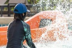 Mädchen ist Spritzwasser im Wasserpark lizenzfreie stockfotografie