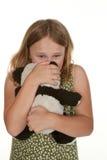 Mädchen ist umgekippt und gibt ihrem Bären eine Liebkosung lizenzfreie stockbilder