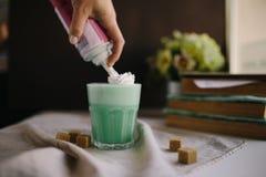 Mädchen ist verzieren Creme in der Schale grünem tadellosem Kaffee Milchshake, cocktaill, frappuccino Lizenzfreie Stockfotografie
