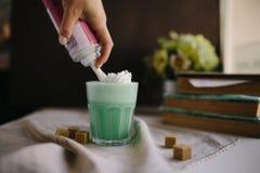 Mädchen ist verzieren Creme in der Schale grünem tadellosem Kaffee Milchshake, cocktaill, frappuccino Lizenzfreies Stockbild