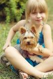 Mädchen 6 Jahre alt auf dem Gras, das Yorkshire Terrier hält Stockbild