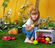 Mädchen 6 Jahre alt im Garten mit Äpfeln Stockbild