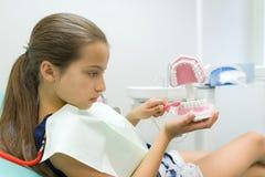 Mädchen 10 Jahre alt im zahnmedizinischen Stuhl, mit Zahnbürste Medizin-, Zahnheilkunde-und Gesundheitswesen-Konzept stockfotos