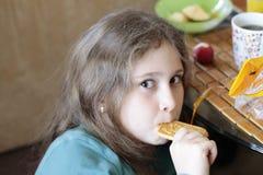 Mädchen 10 Jahre alte Essenplätzchen Heller ausdrucksvoller Blick, Porträt im Weichzeichnungsunschärfehintergrund lizenzfreies stockbild