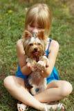 Mädchen 6 Jahre alte Sitzen auf dem Gras und den Griffen Yorkshire Terrier Lizenzfreies Stockfoto