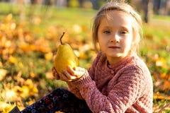 Mädchen 4 Jahre alte Wege im Herbstpark, der eine Birne hält lizenzfreie stockbilder