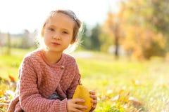 Mädchen 4 Jahre alte Wege im Herbstpark, der eine Birne hält stockfoto