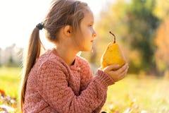 Mädchen 4 Jahre alte Wege im Herbstpark, der eine Birne hält lizenzfreies stockbild