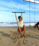 Mädchen 11 Jahre in der Hängematte auf dem Strand mit Meer im Hintergrund Lizenzfreies Stockbild
