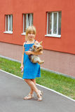 Mädchen 6 Jahre mit Yorkshire-Terrier in ihren Armen nähern sich hohem Gebäude Stockbilder