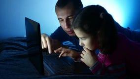 Mädchen jugendlich und Mannvater und Tochter, die am Laptop, das Internet-Spiel im on-line-Unterhaltungsspiel arbeitet stock video