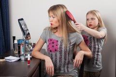 Mädchen kämmt das Haar der Mutter Stockfotografie