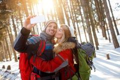 Mädchen küssen ihren Freund im schneebedeckten Wald lizenzfreie stockfotografie
