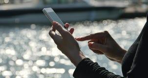 Mädchen 4k A, das einen Smartphone an der Küste, an der Yacht u. am Segeln im Hafen verwendet stock video footage