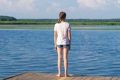 Mädchen kam zum Fluss, Yoga an einem sonnigen Tag, hintere Ansicht zu üben lizenzfreies stockfoto