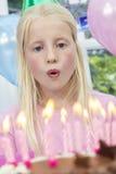 Mädchen-Kind, das heraus Geburtstag-Kuchen-Kerzen durchbrennt Stockfoto