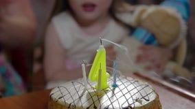 Mädchen klatscht und brennt heraus Kerzen auf Geburtstagskuchen durch stock video footage