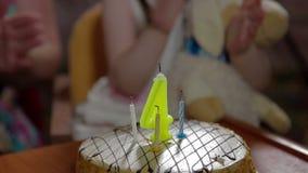 Mädchen klatscht und brennt heraus Kerzen auf Geburtstagskuchen durch stock video
