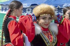 Mädchen kleiden das andere Mädchen im Bashkir nationalen Kostüm an der Sabantuy-Feier Front View stockbild