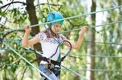 Mädchen klettert zu den hohen Seilstrukturen Stockfotos
