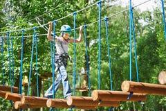 Mädchen klettert zu den hohen Seilstrukturen Stockfotografie