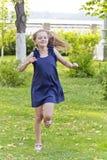 Mädchen laufen in grünen Park mit dem ungepflegten Haar Stockfotografie