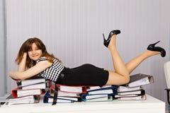 Mädchen legen bequem auf Dokumenten nieder Lizenzfreies Stockfoto