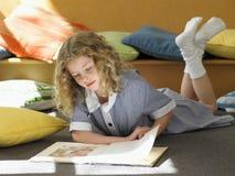 Mädchen-Lesebuch auf Boden im Klassenzimmer Lizenzfreies Stockbild