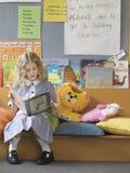 Mädchen-Lesebuch auf Couch im Klassenzimmer Stockfotografie